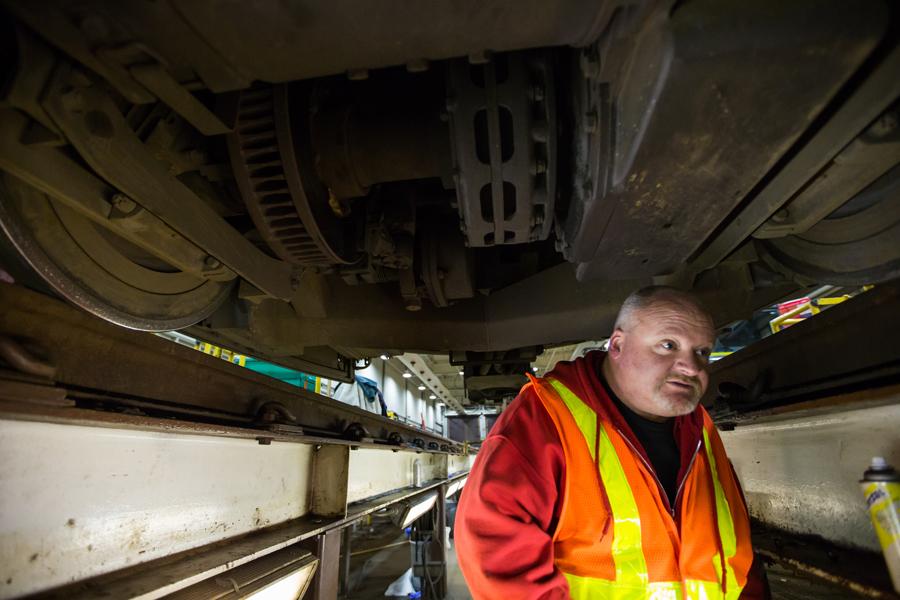 Igoe walks beneath a train at the depot.