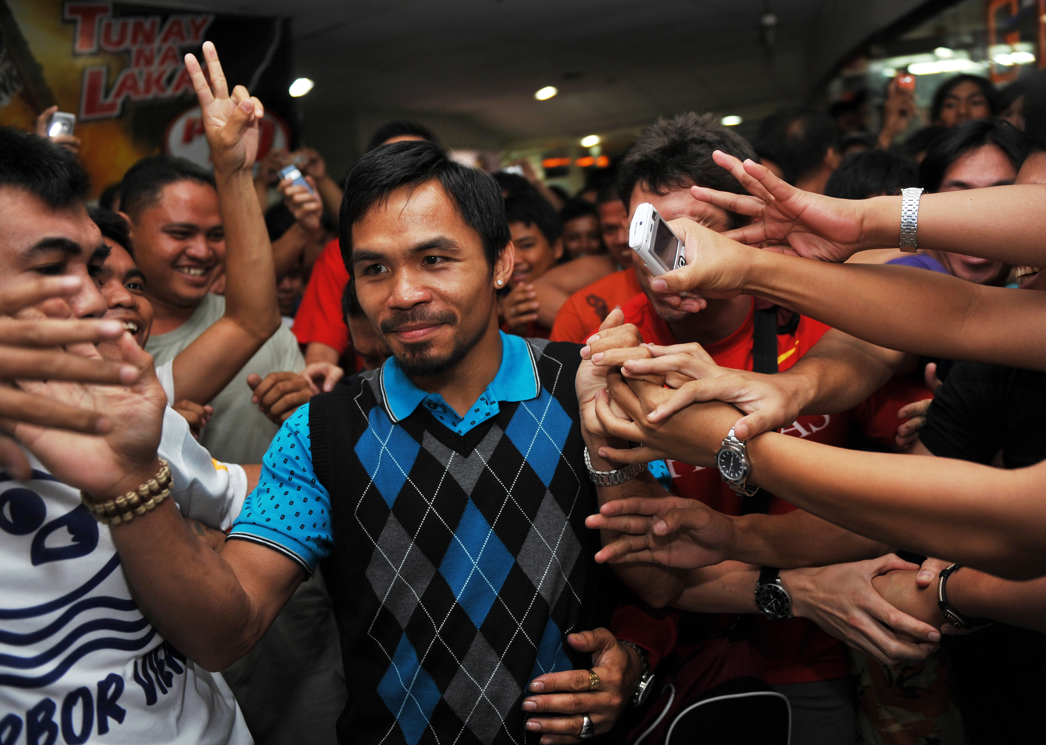 To go with AFP story by Mynardo Macaraig Philippine boxing hero Manny Pacquiao (C) is mobbed by fans after a training session outside a gym in Manila on October 22, 2009.  For the Philippines, boxer Manny Pacquiao is more than a sports champion. His fans, the media and politicians see him as nothing less than a national hero whose feats can lift the nation.        AFP PHOTO/TED ALJIBE (Photo credit should read TED ALJIBE/AFP/Getty Images)