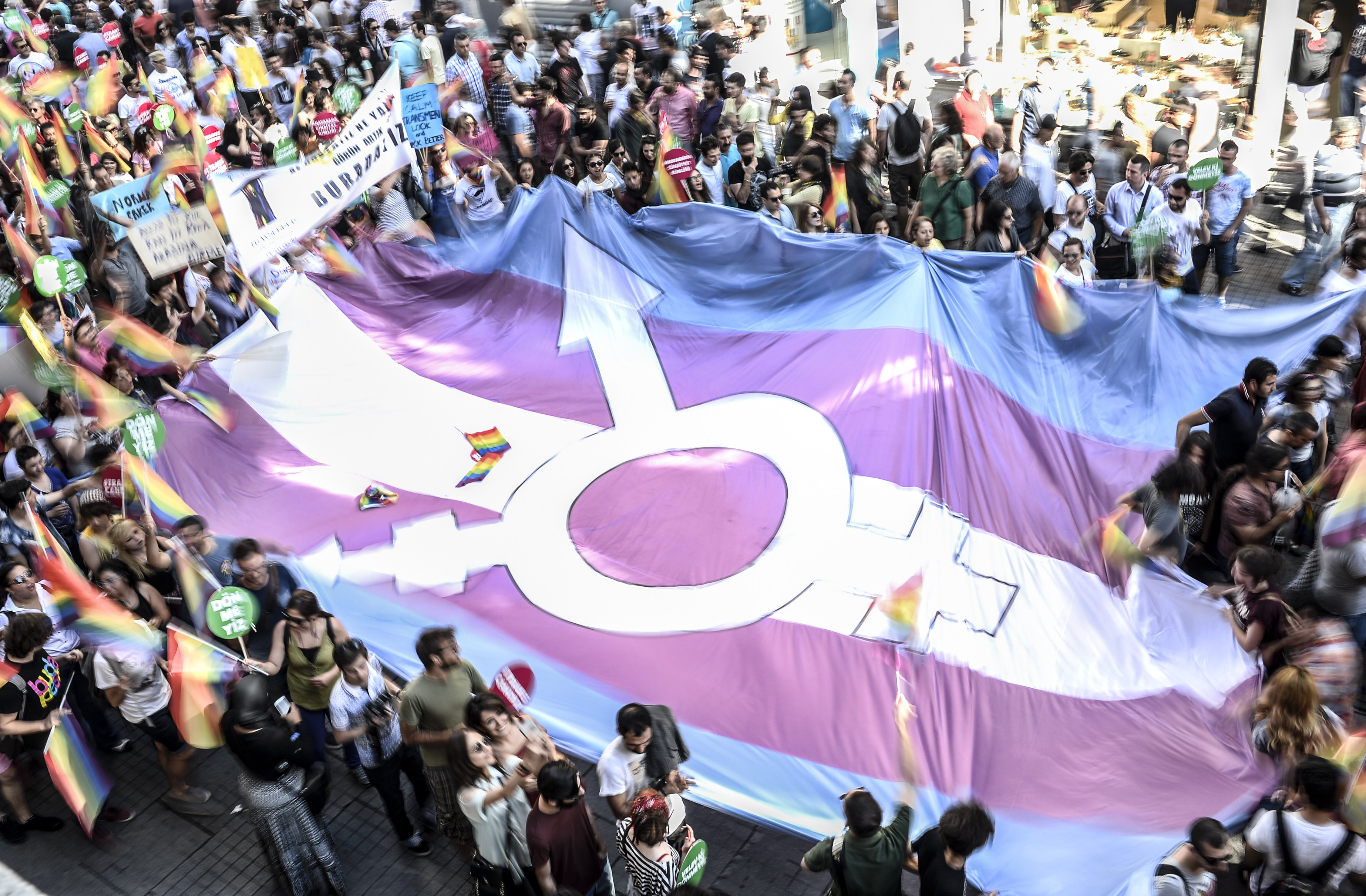 People hold a giant transgender flag during a gay parade on Istiklal Street, the main shopping corridor in Istanbul, on June 22, 2014, during the Trans Pride Parade as part of the Trans Pride Week 2014, which is organized by Istanbul's 'Lesbians, Gays, Bisexuals, Transvestites and Transsexuals' (LGBTT) solidarity organization. AFP PHOTO/BULENT KILIC        (Photo credit should read BULENT KILIC/AFP/Getty Images)