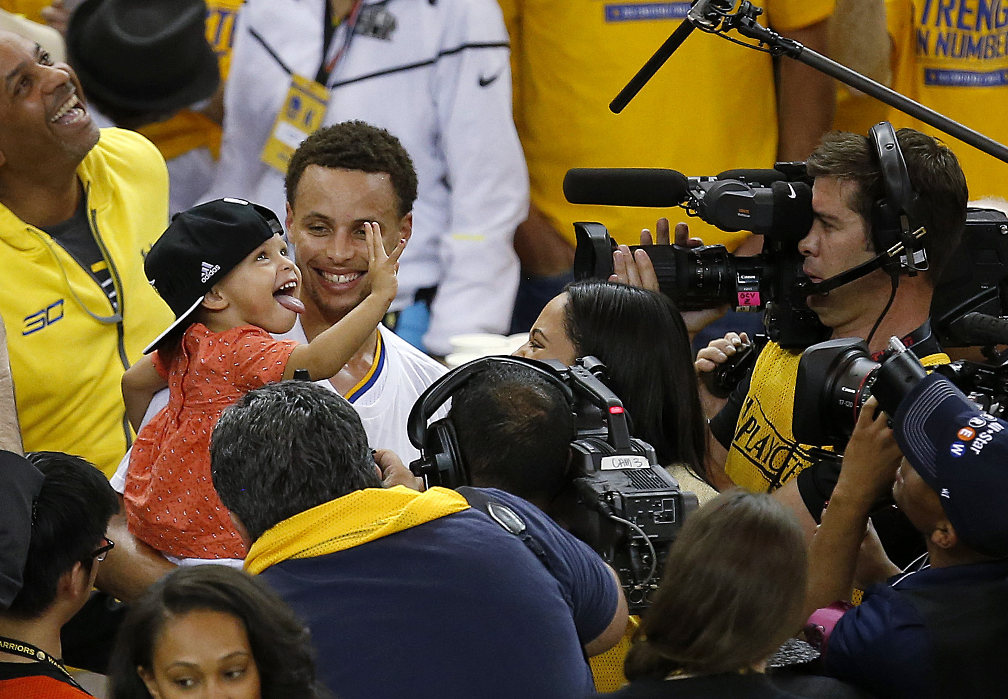 Golden State Warriors guard Stephen Curry holds his daughter Riley after Game 5 of the NBA basketball Western Conference finals against the Houston Rockets in Oakland, Calif., Wednesday, May 27, 2015. The Warriors won 104-90 and advanced to the NBA Finals. (AP Photo/Tony Avelar)
