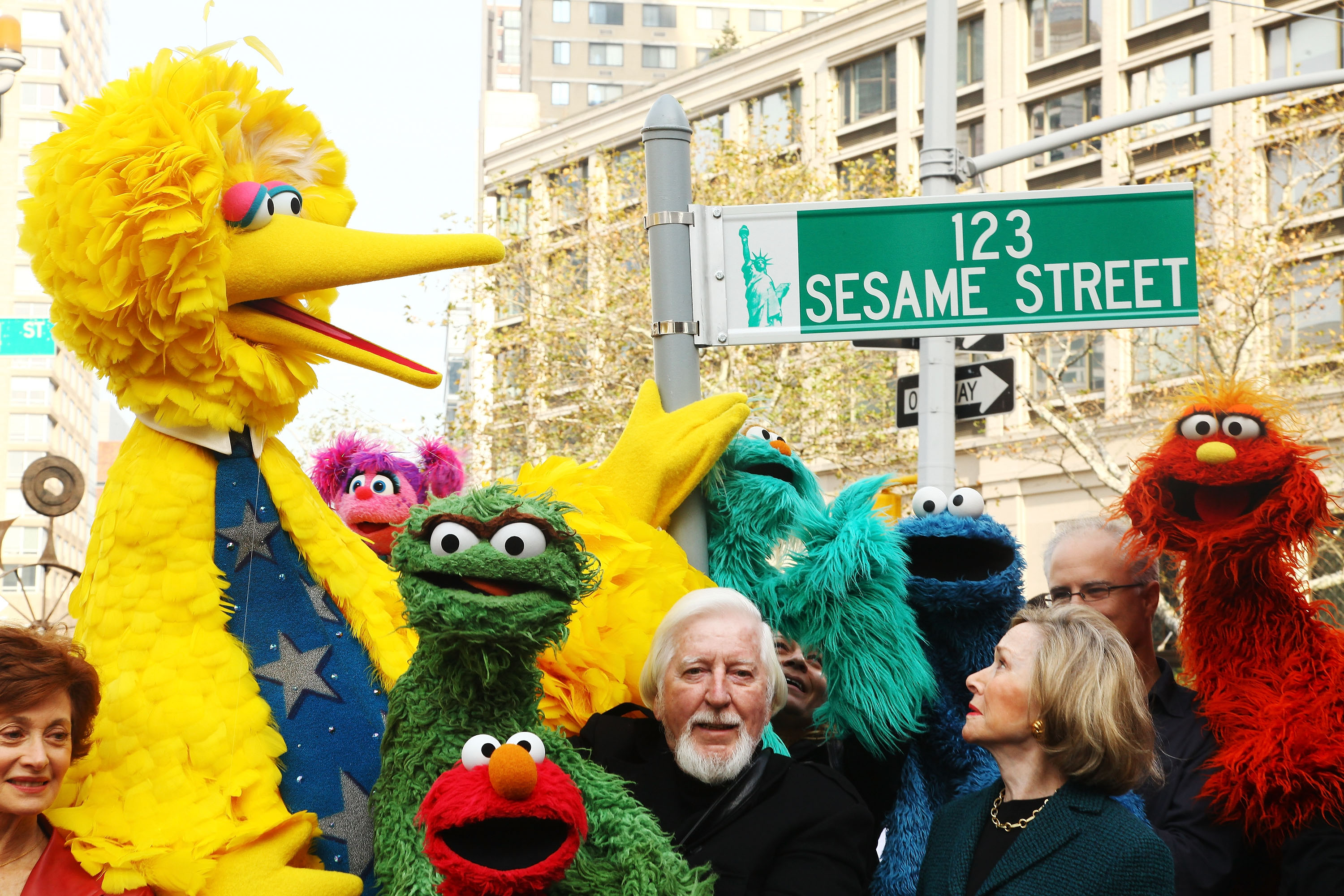 "NEW YORK - NOVEMBER 09: (L-R) Puppeteer Caroll Spinney, Sesame Street co-founder and TV producer Joan Ganz Cooney, and Sesame Street cast members pose under a ""123 Sesame Street"" sign at the ""Sesame Street"" 40th Anniversary temporary street renaming in Dante Park on November 9, 2009 in New York City. (Photo by Astrid Stawiarz/Getty Images)"
