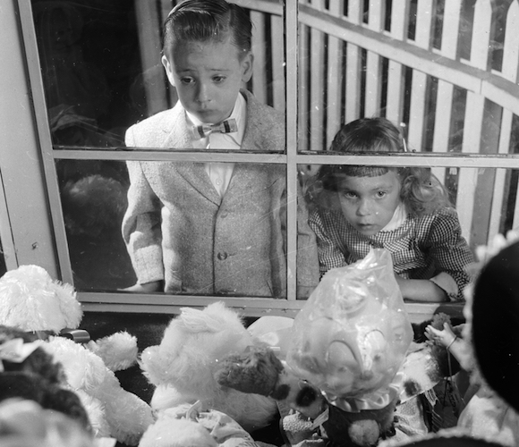 circa 1955:  A young boy and girl stare through a window at a selection of toys at the Ideal Toy Company in Jamaica, Long Island, USA. The company is one of the largest toy producers in the world.  (Photo by Orlando /Three Lions/Getty Images)