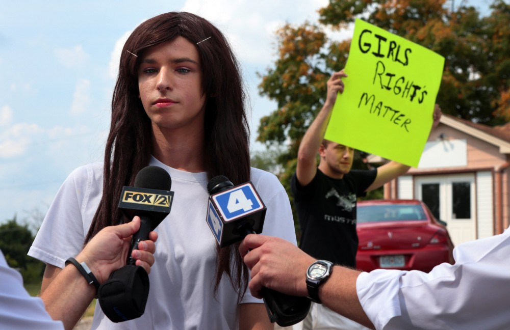 In a Monday, Aug. 31, 2015 photo, Lila Perry, a Hillsboro High School senior and transgender student, speaks with reporters as Blayke Childs, back, offers his opinion after a student walkout at Hillsboro High School over Perry's request to use the girls bathrooms and locker rooms rather than a unisex faculty bathroom.  (Robert Cohen/St. Louis Post-Dispatch via AP)  EDWARDSVILLE INTELLIGENCER OUT; THE ALTON TELEGRAPH OUT; MANDATORY CREDIT