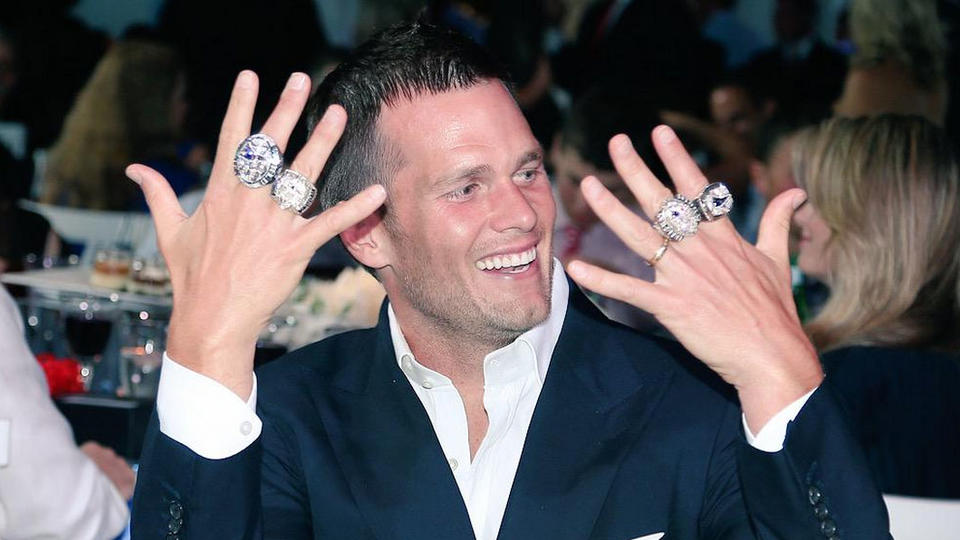 (Brookline, MA, 0/14/15) New England quarterback Tom Brady holds his hands with all four of his Super Bowl rings during a ceremony on Sunday, June 14, 2015. Photo courtesy of the New England Patriots
