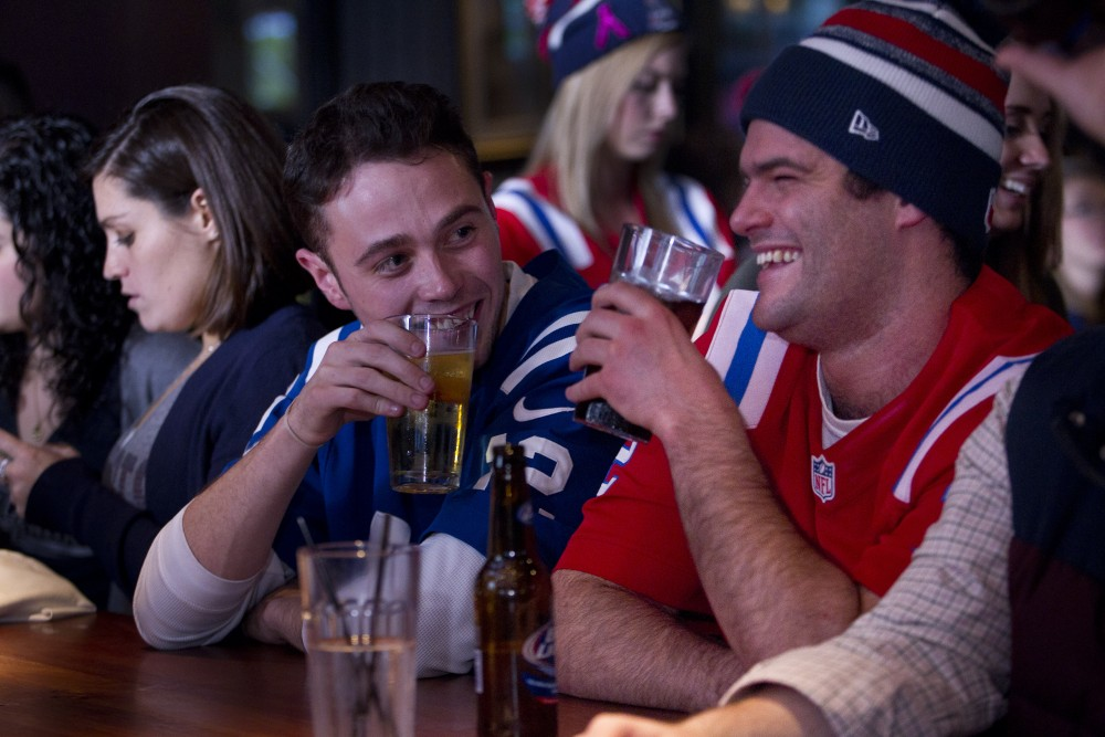 01/18/2015 - Boston, MA - Topic: 19patsfans  - Indiana Colts fan Jack Cox, cq, of Nashville, TN (in blue) and Patriots fan Derek Keith, cq, of Hamilton, MA, watched the AFC playoffs matchup featuring their two teams while sipping beers at the Cask 'n Flagon (cq) in Boston on Sunday evening, January 18, 2015. The two met while in school at Indiana University. Story by Zolan Kanno-Youngs. Photo by Dina Rudick/Globe Staff.
