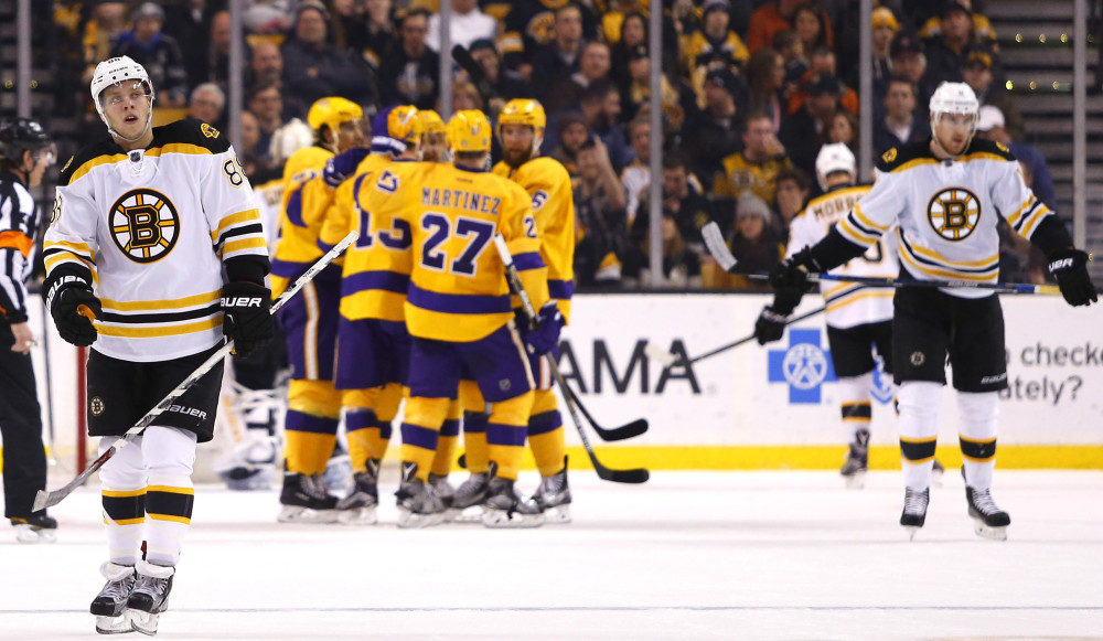 Boston Bruins' David Pastrnak, left, and Jimmy Hayes, right, skate back to the bench as the Los Angeles Kings celebrate a goal during the second period of the Los Angeles Kings 9-2 win over the Boston Bruins in an NHL hockey game in Boston Tuesday, Feb. 9, 2016. (AP Photo/Winslow Townson)
