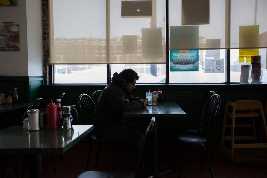 Hani Hasan Bajamal flips through his phone at a window table.