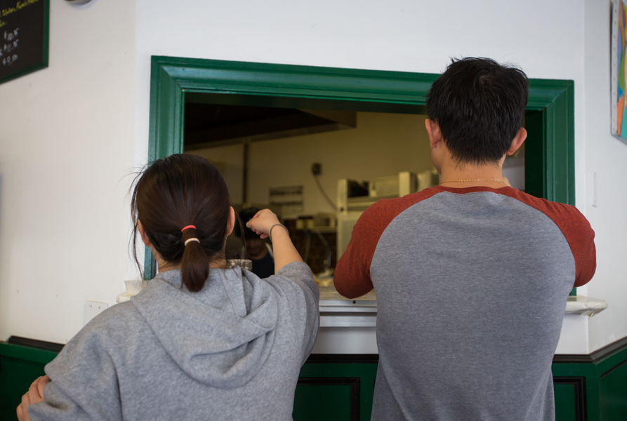 Catherine Taing and Leng Hong manage orders at the kitchen window.