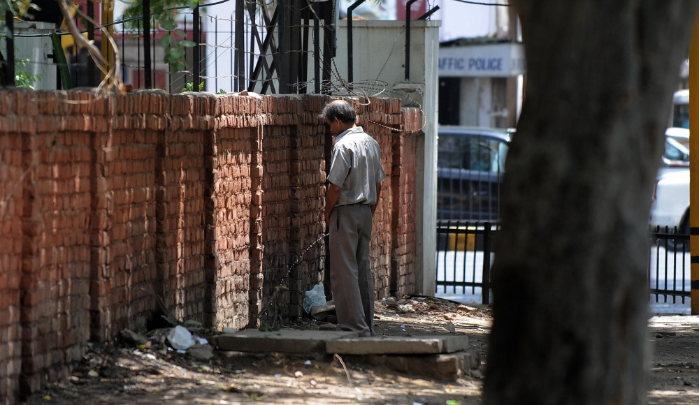 An Indian man urinates against a wall in