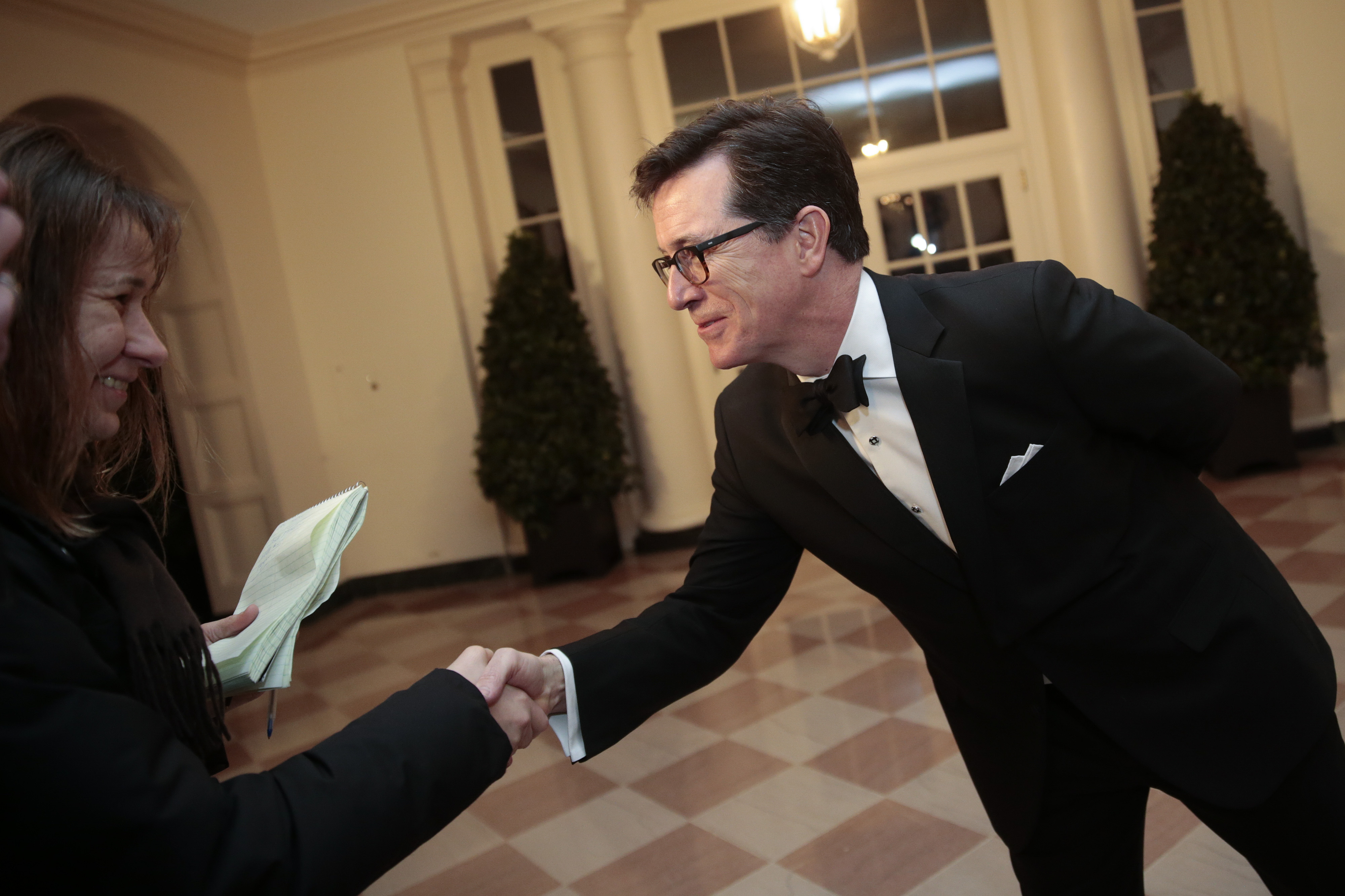 WASHINGTON, DC - FEBRUARY 11:  Actor and television host Stephen Colbert, right, greets a member of the French press as he arrives to a state dinner hosted by U.S. President Barack Obama and U.S. first lady Michelle Obama in honor of French President Francois Hollande at the White House on February 11, 2014 in Washington, DC. Obama and Hollande said the U.S. and France are embarking on a new, elevated level of cooperation as they confront global security threats in Syria and Iran, deal with climate change and expand economic cooperation. (Photo by Andrew Harrer-Pool/Getty Images)