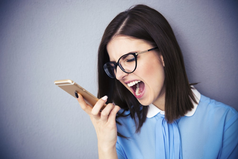 Angry businesswoman shouting on smartphone