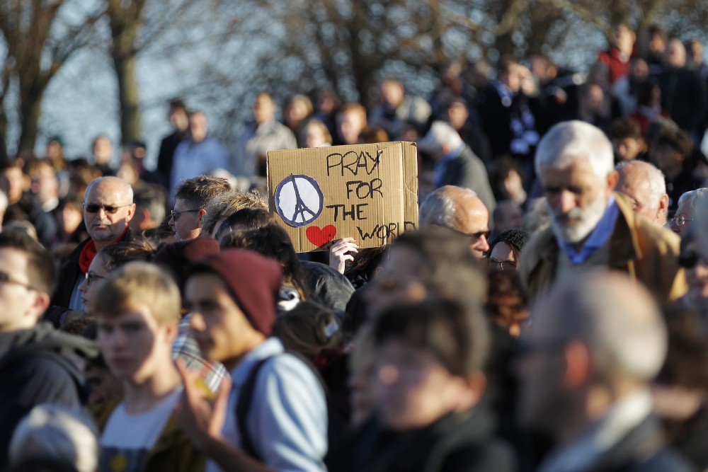 """A demonstrator holds a placard reading """"pray for the world"""" during a demonstration in front of the Memorial of Caen in tribute to the victims of the Paris attacks on November 15, 2015 in Caen. The string of coordinated attacks in and around Paris on November 13 left more than 120 people dead, in the worst such violence in France's history. The assailants struck six different sites, including the Stade de France football stadium and eateries in the trendy east of the city. AFP PHOTO / CHARLY TRIBALLEAUCHARLY TRIBALLEAU/AFP/Getty Images"""